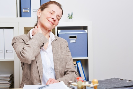 senior business: Senior business woman stretching with neck pain in her office