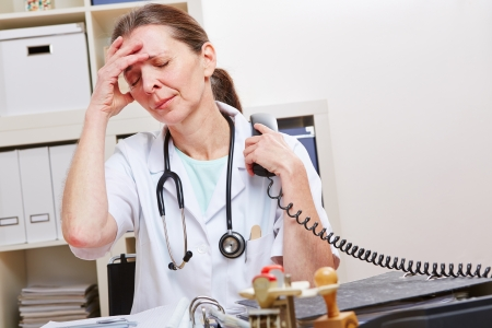 doctor burnout: Doctor with burnout snydrome in office at the phone