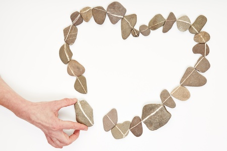 friendship day: Hand putting stone to other stones in love heart shape