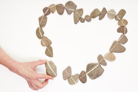 amistad: Mano de piedra para poner otras piedras en forma de coraz�n del amor Foto de archivo