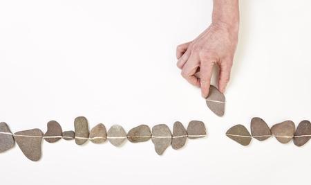 Hand, die einen Stein in der Reihe der vielen Kieselsteinen