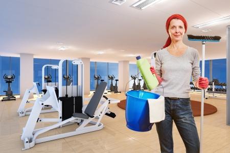mujer limpiando: Señora de la limpieza mayor con los productos de limpieza de pie en un gimnasio Foto de archivo