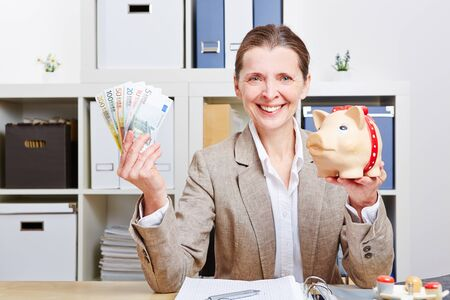 Happy elderly business woman with piggy bank and Euro money in her office Stock Photo - 18127614