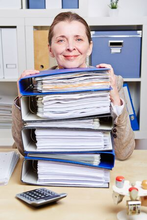 administration: Smiling senior business woman with files on her desk in her office