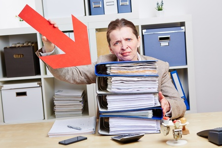Business woman with burnout pointing arrow to files in her office photo