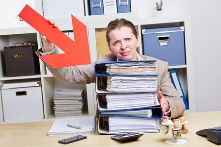 administracion de empresas: Mujer de negocios con la flecha apuntando a los archivos de burnout en su oficina Foto de archivo