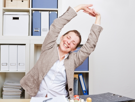 old office: Senior business woman with back pain stretching in her office