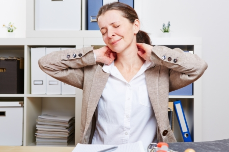 stretches: Senior business woman with pain massaging her neck in her office