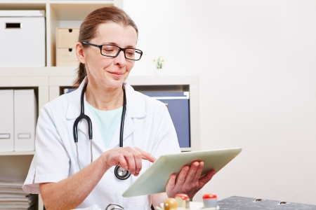 doctor tablet: Senior female doctor using a tablet computer in her office