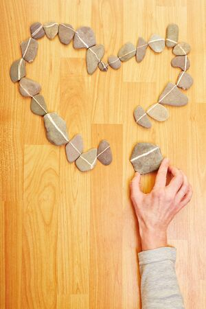 Hand putting stone to stones in love heart shape photo