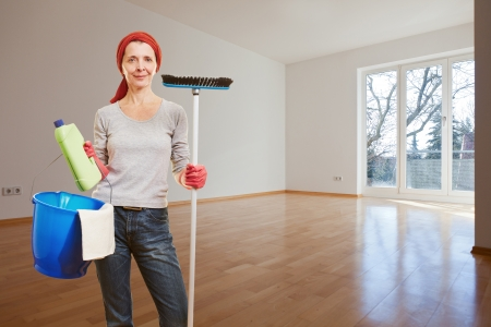 Senior woman with cleaning supplies making spring cleaning in apartment room photo