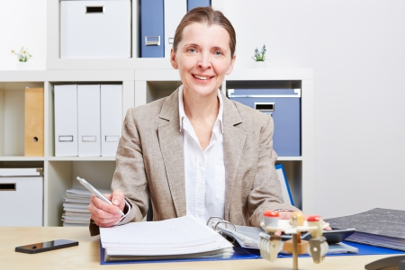 Happy elderly business woman sitting with files in her office photo