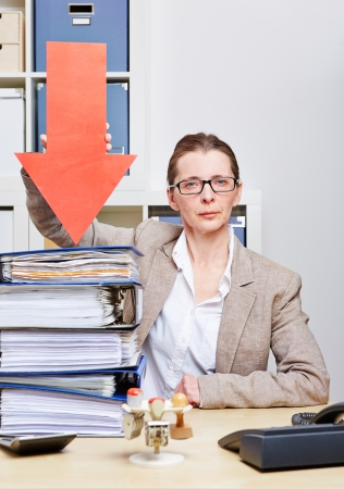 Strict business woman in her office pointing arrow to stack of files photo