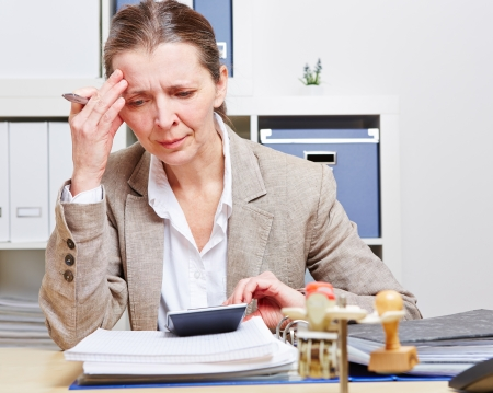 Business woman with burnout sitting in her office at the desk over files photo