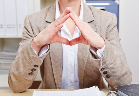 hand position: Body language of a senior business woman in her office