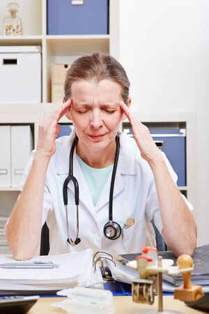 Frustrated doctor with headache in office massaging her temples Stock Photo - 18185870