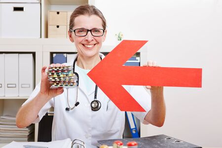 Happy female doctor pointing red arrow to medical pills in her office Stock Photo - 18185862