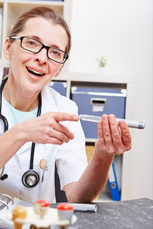 Senior doctor explaining syringe for insulin injection in her office Stock Photo - 18185878
