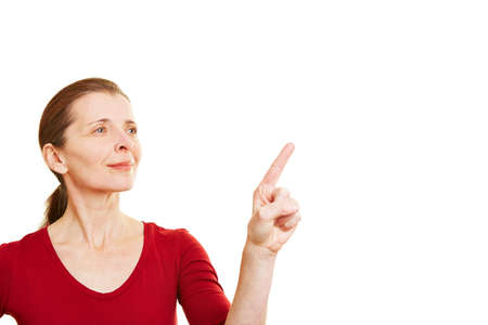 Senior woman pointing with her index finger to invisible touchscreen Stock Photo - 18232161