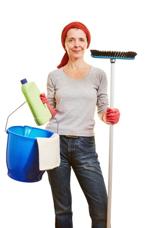 Happy elderly housewife with different cleaning products photo