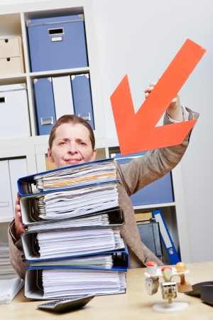 Stressed business woman pointing with arrow to stack of files photo