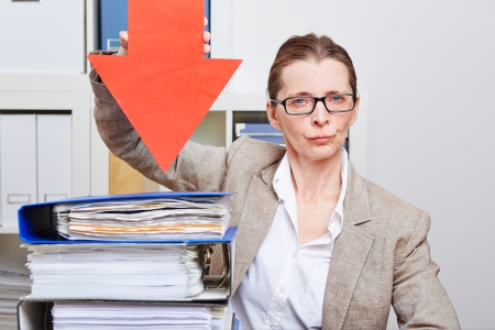 Serious business woman in her office pointing with arrow to many files Stock Photo - 18208989