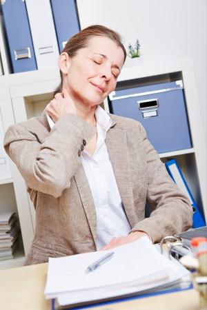 collo: Anziana donna d'affari dolore sentimento nel suo collo nel suo ufficio