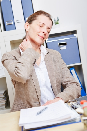 back exercise: Elderly business woman feeling pain in her neck in her office Stock Photo