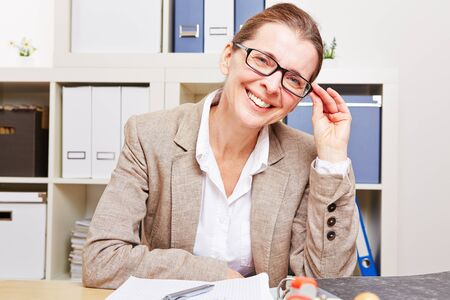 Nearsighted business woman with glasses sitting at her desk in the office photo