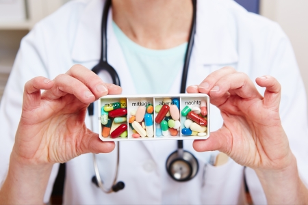 pill box: Doctor hands holding many colorful tablets in pill box