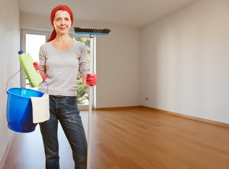 Senior cleaning lady with cleaning products standing in an empty apartment room photo