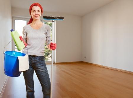 Senior femme de m�nage avec des produits de nettoyage debout dans une chambre appartement vide