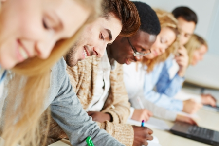 classroom training: Happy students in a seminar studying for a test in a university Stock Photo