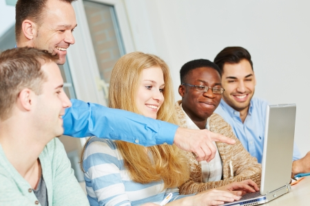 Happy school teacher pointing with his hand to laptop computer in class Stock Photo - 18372928