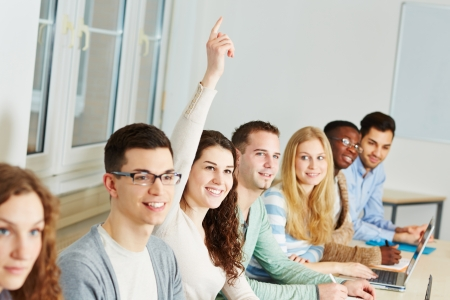Young smiling woman raising her hand in a university class photo