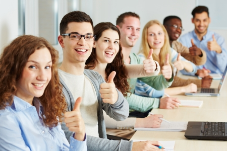 dual: Many happy students holding their thumbs up in class