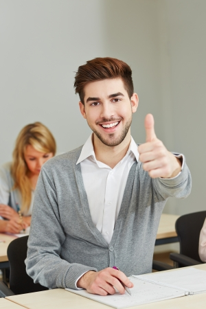 happy young student holding his thumbs up in university class photo