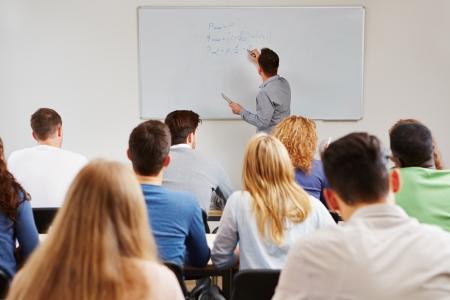 teacher: Profesor en la pizarra de clase de negocios en los estudios de ense�anza en la universidad Foto de archivo