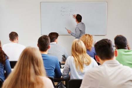 Teacher on whiteboard in class teaching business studies in university photo