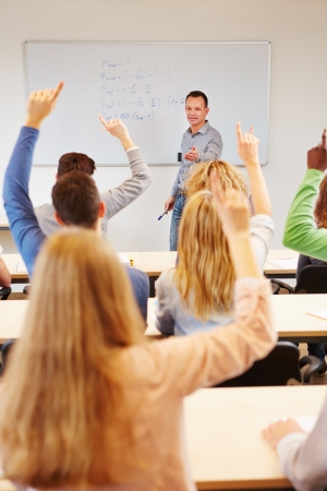 Students answering question in school class with teacher on whiteboard photo