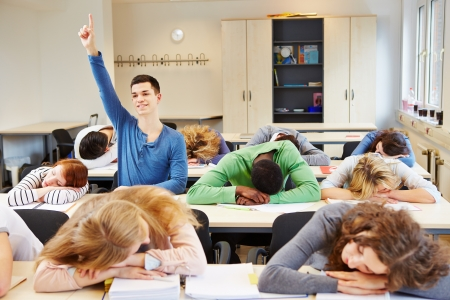 diligent: Sleeping students and diligent pupil in a school classroom