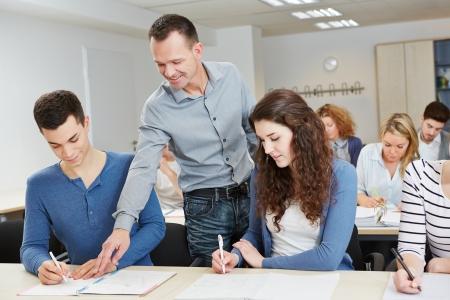 high school teacher: Teacher helping pupil in school class in a classroom