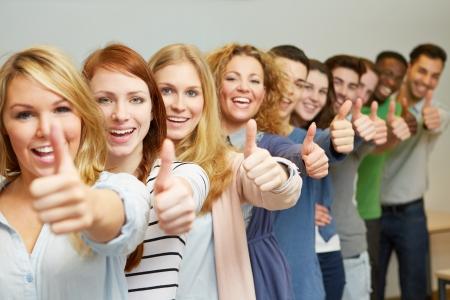 Molti studenti di successo che tengono i pollici in su in una fila
