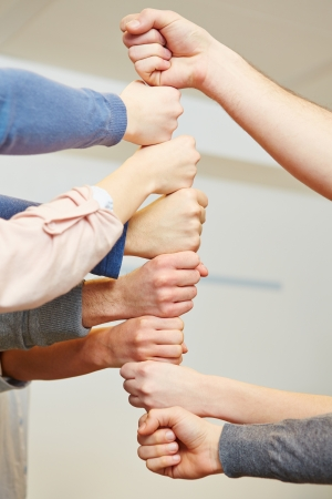 Many students stacking their fists as teamwork symbol Stock Photo - 18278461