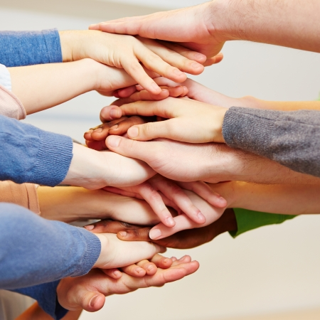 Business team cooperation with many hands stacked on top