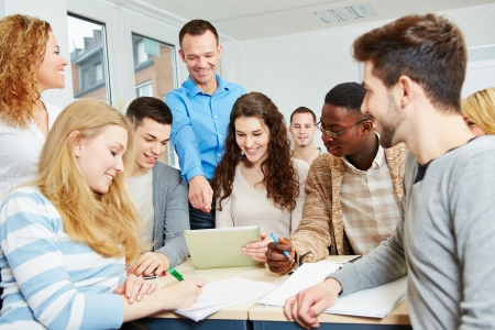 computer education: Happy students learning with teacher in university class