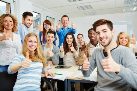 Many happy students with teacher holding their thumbs up in university