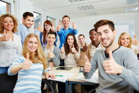 estudantes: Muitos estudantes felizes com o professor segurando seus polegares na universidade
