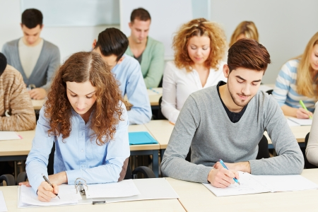 Many students in lecture in university classroom taking notes