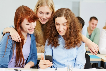 Three happy women checking social media with a smartphone in university photo